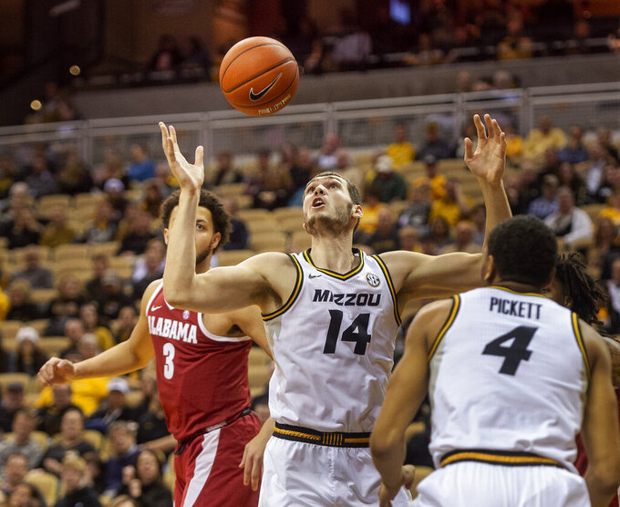 Missouri's Reed Nikko, center, pulls down a rebound between teammate Javon Pickett, right, and Alabama's Alex Reese, left, during the first half of an NCAA college basketball game, Wednesday, Jan. 16, 2019, in Columbia, Mo. (AP Photo/L.G. Patterson)