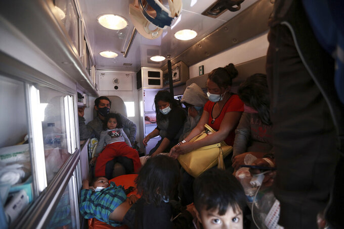 Migrants deported from the U.S. sit in an ambulance as they are driven to a shelter in Ciudad Juarez, Mexico, Tuesday, March 23, 2021. Mexico announced that U.S. advisers on border and immigration issues will meet with Mexican officials on Tuesday to discuss migration and development in Central America, as a surge of migrants has hit the U.S. southern border. (AP Photo/Christian Chavez)