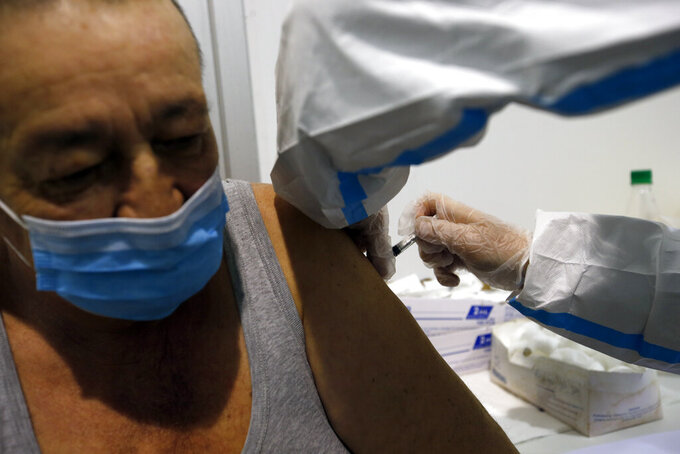 A medical worker administers a shot of COVID-19 vaccine to a man in Belgrade, Serbia, Wednesday, Feb. 17, 2021. Serbia, a country of 7 million, has so far vaccinated some 1 million people, mainly with the Chinese Sinopharm vaccine and Russian Sputnik V, and to a lesser extent with the Pfizer jab. (AP Photo/Darko Vojinovic)