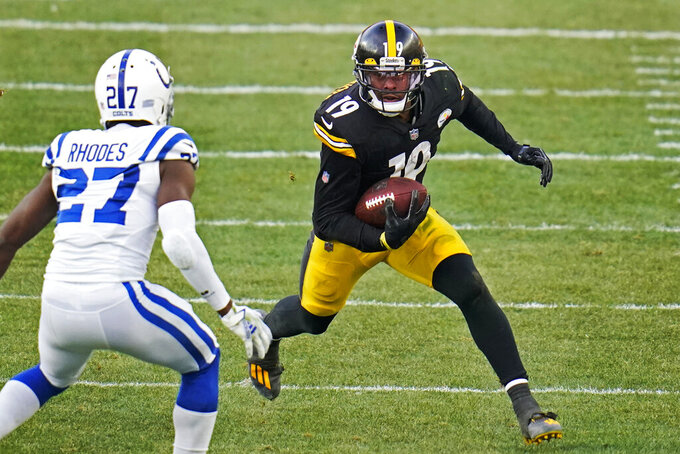 "File-This Dec. 27, 2020, file photo shows Pittsburgh Steelers wide receiver JuJu Smith-Schuster (19) running after a catch with Indianapolis Colts cornerback Xavier Rhodes (27) defending during the second half of an NFL football game in Pittsburgh. Smith-Schuster is keeping it ""lit"" with the Pittsburgh Steelers. The free-agent wide receiver surprisingly opted to return to the Steelers on Friday just days after strongly hinting that his departure on the open market was imminent. (AP Photo/Gene J. Puskar, File)"