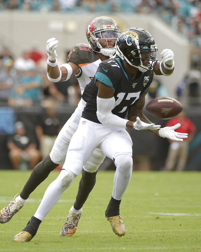 Jacksonville Jaguars wide receiver D.J. Chark (17) makes a reception in front of Tampa Bay Buccaneers cornerback Carlton Davis, left, during the second half of an NFL football game, Sunday, Dec. 1, 2019, in Jacksonville, Fla. (AP Photo/Phelan M. Ebenhack)