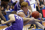 Kansas guard Chris Teahan, right, tangles with Kansas State forward Pierson McAtee (24) during the second half of an NCAA college basketball game in Lawrence, Kan., Tuesday, Jan. 21, 2020. Kansas defeated Kansas State 81-59. (AP Photo/Orlin Wagner)