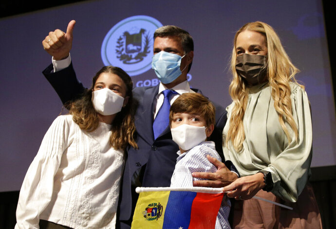 Venezuelan opposition leader Leopoldo Lopez with his wife Lilian Tintori and their son and daughter pose for a photo after a news conference in Madrid on Tuesday, Oct. 27, 2020. Prominent opposition activist Leopoldo López who has abandoned the Spanish ambassador's residence in Caracas and left Venezuela after years of frustrated efforts to oust the nation's socialist president is holding a news conference in Madrid. (AP Photo/Andrea Comas)