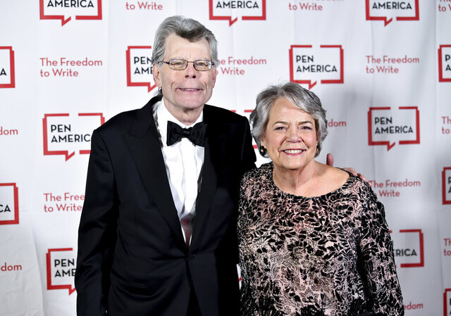 """FILE - In this May 22, 2018 file photo, PEN literary service award recipient Stephen King poses with Simon & Schuster president Carolyn Reidy at the 2018 PEN Literary Gala at the American Museum of Natural History on in New York.  ViacomCBS, fresh off a merger, is looking to sell its Simon & Schuster book publishing business as it tries to raise cash to pay down debt and please shareholders with dividends and stock buybacks. ViacomCBS CEO Bob Bakish said the book publisher is not a """"core asset"""" of the company since it isn't video. But he said it's a """"marquee asset"""" that is """"highly valuable."""" (Photo by Evan Agostini/Invision/AP, File)"""