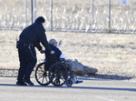 STERLING, CO - JANUARY 15: A Sterling Correctional Facility guard, left, rolls Anthony Martinez to an awaiting niece, Kelly Brasier, (not pictured) in the parking lot of the prison Friday, Jan. 15, 2021 in Sterling, Colo.. Anthony Martinez, 84, suffering from dementia, was released from the Sterling Correctional Facility Friday after serving over 30-years in prison burglary and habitual offenses, Governor Polis commuted his sentence. Kelly is taking Anthony back home to Pennsylvania to take care of him. (Andy Cross/The Denver Post via AP)