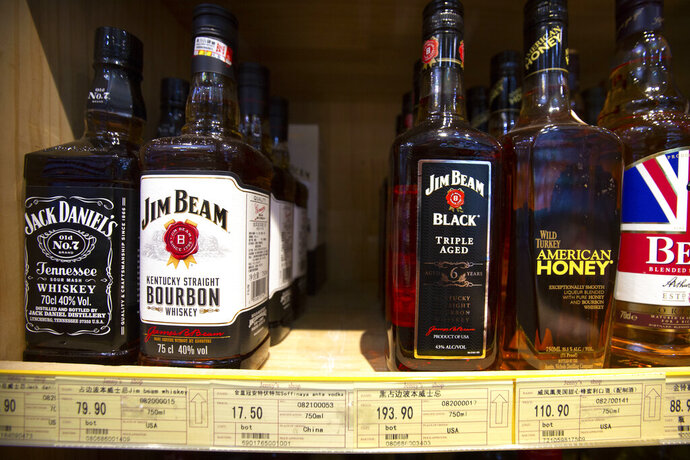 In this July 7, 2018 file photo whiskeys distilled and bottled in the U.S. are displayed for sale in a grocery store in Beijing. American whiskey distillers have watched more than $300 million in export revenues evaporate in the two years since becoming entangled in a trade dispute between the Trump administration and the European Union, according to estimates in a new report. Exports of American whiskey — mostly bourbon, Tennessee whiskey and rye whiskey — to the EU have fallen 33% since the EU imposed a retaliatory tariff on those products on June 22, 2018, according to the report issued Monday, June 22, 2020 by the Distilled Spirits Council of the United States. (AP Photo/Mark Schiefelbein, file)