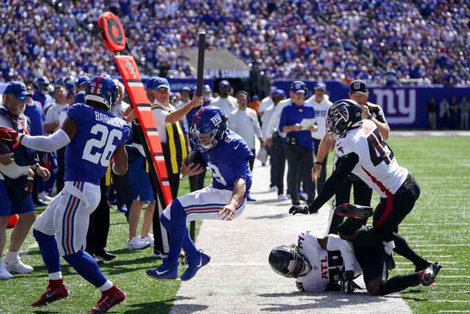 New York Giants quarterback Daniel Jones (8) runs the ball out of bounds on a play against Atlanta Falcons defensive back T.J. Green (39) and linebacker Deion Jones (45) during the first half of an NFL football game, Sunday, Sept. 26, 2021, in East Rutherford, N.J. (AP Photo/Seth Wenig)
