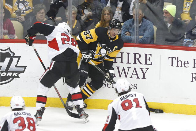 Pittsburgh Penguins' Sidney Crosby (87) looks to pass as Ottawa Senators' Connor Brown defends during the first period of an NHL hockey game, Tuesday, March 3, 2020, in Pittsburgh. (AP Photo/Keith Srakocic)
