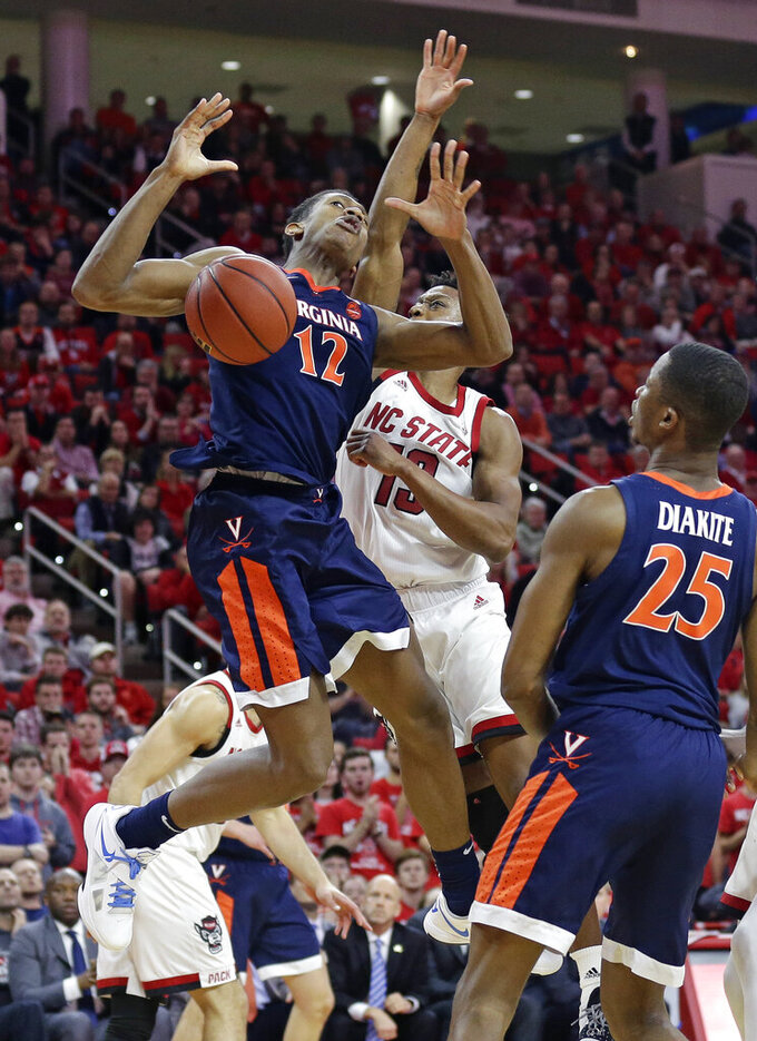 Virginia's De'Andre Hunter (12) loses the ball while driving to the basket against North Carolina State's C.J. Bryce while Virginia's Mamadi Diakite (25) watches during the second half of an NCAA college basketball game in Raleigh, N.C., Tuesday, Jan. 29, 2019. Virginia won 66-65 in overtime. (AP Photo/Gerry Broome)