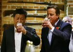 """FILE - In this Thursday, Oct. 22, 2015 file photo, Britain's Prime Minister David Cameron, right, drinks beer with Chinese President Xi Jinping, at a pub in Princess Risborough, near Chequers, England. Only five years ago, former British Prime Minister David Cameron was celebrating a """"golden era"""" in U.K.-China relations, bonding with President Xi Jinping over a pint of beer at the pub and signing off trade deals worth billions. Those friendly scenes now seem like a distant memory, with hostile rhetoric ratcheting up this week over Beijing's new national security law on Hong Kong. China has threatened """"consequences"""" after Britain offered refuge to millions in the former colony.  (AP Photo/Kirsty Wigglesworth, file)"""
