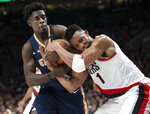 New Orleans Pelicans guard Jrue Holiday and Portland Trail Blazers forward Evan Turner vie for the ball during the first half in Game 1 of an NBA basketball first-round playoff series Saturday, April 14, 2018, in Portland, Ore. (AP Photo/Randy L. Rasmussen)