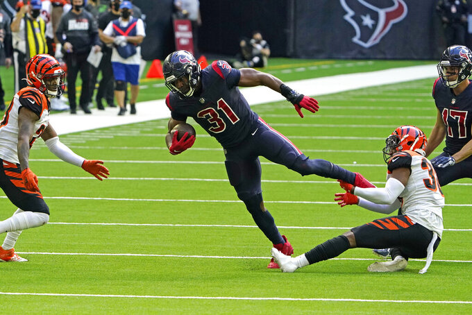 Houston Texans running back David Johnson (31) is tackled by Cincinnati Bengals cornerback LeShaun Sims, right, after gaining 48 yards during the second half of an NFL football game Sunday, Dec. 27, 2020, in Houston. (AP Photo/Eric Christian Smith)