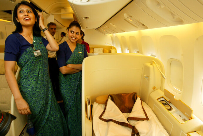 FILE - In this July 30, 2007, file photo, Air India's stewardesses explain facilities available to First Class travelers in their Boeing 777-200 LR aircraft during a function held to mark its commencement of operations, at the Chattrapati Shivaji International airport in Mumbai, India. Cash-starved Air India is putting its crew on a diet, changing their inflight menu to special low-fat meals. Dhananjay Kumar, the state-run airline's spokesman, said Wednesday, Sept. 18, 2019, that the objective is to provide healthy and cost-effective meals to crews on domestic and international flights. In 2009, the airline fired 10 air hostesses for being overweight after they failed to get back in shape three years after they were switched to ground crew jobs. (AP Photo/Gautam Singh, File)
