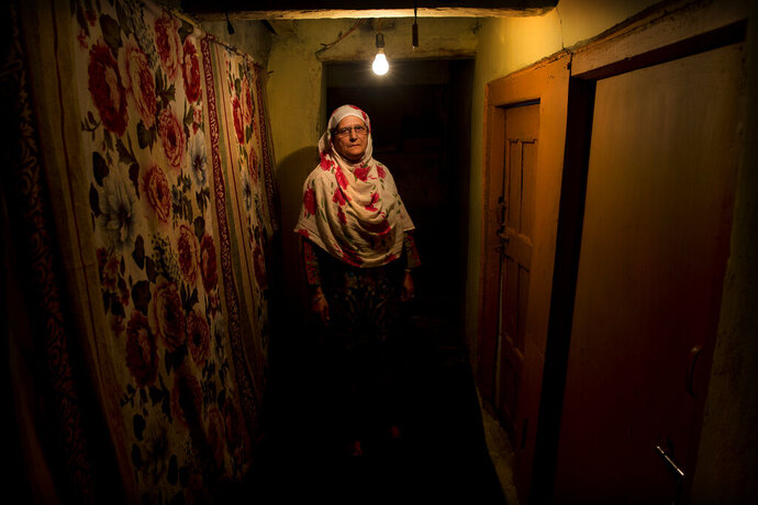 """In this Sept. 25, 2019, photo, Ateeqa Begum, mother of a 22-year-old Kashmiri detainee Fasil Aslam Mir, stands for a photograph inside her house in Srinagar, Indian controlled Kashmir. Begum has lived alone ever since her only son Fasil, in his late twenties, was detained on his way home after fetching medicines for her. """"My son has been shifted to a jail in an Indian city and I have no means to travel there to see him,"""" she said. (AP Photo/ Dar Yasin)"""