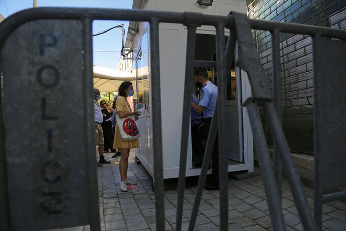 A woman wearing protective face mask, shows her PCR test to an officer at Ledra crossing point in divided capital Nicosia, Cyprus, Friday, June 4, 2021. Ethnically split Cyprus took a key step toward a return to its normal rhythms of life amid the pandemic on Friday when nine crossing points along a United Nations-controlled buffer zone were reopened, enabling ordinary Cypriots to cross the divide. (AP Photo/Petros Karadjias)