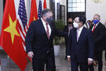 U.S. Secretary of State Mike Pompeo, left, and Vietnamese Foreign Minister Pham Binh Minh walk for a meeting in Hanoi, Vietnam, Friday, Oct. 30, 2020. Pompeo is wrapping up an anti-China tour of Asia in Vietnam as the fierce American presidential election race enters its final stretch. (Bui Lam Khanh/VNA via AP)