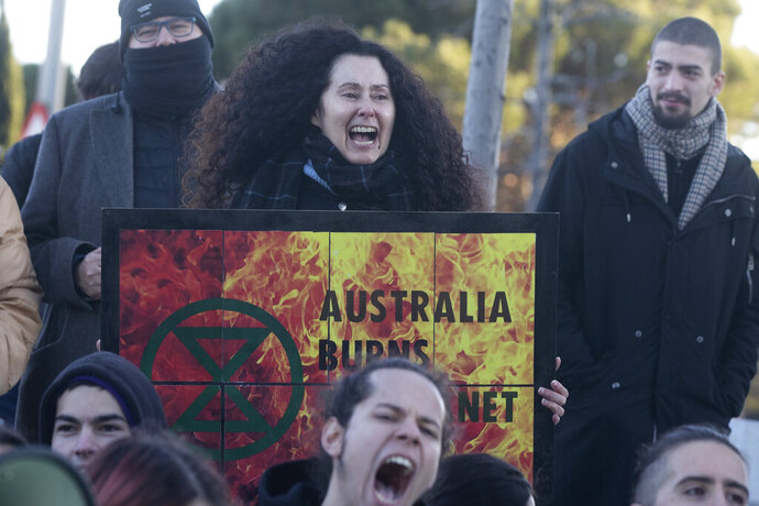 People from the Fridays For Future movement protest outside the Australian Embassy in Madrid, Spain, Friday, Jan.10, 2020. The protest is to demand more climate action and to show solidarity with the critical situation in Australia after more than a month of forest fires. (AP Photo/Paul White)