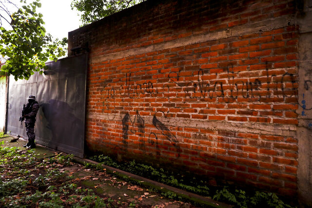 FILE - In this Oct. 10, 2019, file photo police guard next to a graffiti wall with the name of a gang as part of a routine patrol in Lourdes, La Libertad, El Salvador. The Human Rights Watch in the report being released Wednesday, Feb. 5, 2020, said that at least 138 people deported to El Salvador from the U.S. in recent years were subsequently killed. The new report comes as the Trump administration makes it harder for Central Americans to seek refuge here. (AP Photo/Eduardo Verdugo, File)