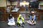 Activist wearing masks to represent those affected by air pollution, sit on the floor in protest before judges announce their verdict on a civil lawsuit filed against several Indonesian officials, including President Joko Widodo and Jakarta Governor Anies Baswedan for their failure to improve poor air quality in the capital city, inside a courtroom at Central Jakarta District Court in Jakarta, Indonesia, Thursday, Sept. 16, 2021. The court ruled Thursday that President Widodo and six other top officials have neglected to fulfill citizens' rights to clean air and ordered them to improve the poor air quality in the capital. (AP Photo/Dita Alangkara)