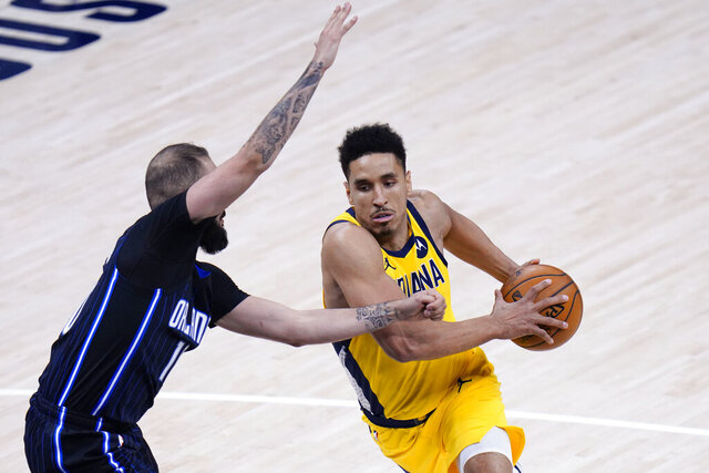 Indiana Pacers guard Malcolm Brogdon, right, goes around Orlando Magic guard Evan Fournier during the second half of an NBA basketball game in Indianapolis, Friday, Jan. 22, 2021. (AP Photo/AJ Mast)