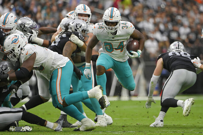 Miami Dolphins running back Malcolm Brown (34) avoids a tackle before running in for a touchdown against the Las Vegas Raiders during the first half of an NFL football game, Sunday, Sept. 26, 2021, in Las Vegas. (AP Photo/David Becker)