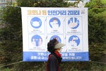 A woman wearing a face mask to help curb the spread of the coronavirus walks by a social distancing sign at a park in Seoul, South Korea, Friday, Oct. 16, 2020. South Korea's daily coronavirus tally has dropped below 50 for the first time in more than two weeks despite reports of small-scale local infections. The sign reads: