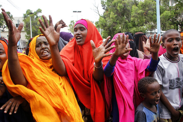 Somali women protest against the killing Friday night of at least one civilian during the overnight curfew, which is intended to curb the spread of the new coronavirus, on a street in the capital Mogadishu, Somalia Saturday, April 25, 2020. A police officer in Somalia's capital has been arrested in the fatal shooting of at least one civilian while enforcing coronavirus restrictions, a fellow police officer said, sparking protests that continued Saturday with crowds of angry young men burning tires and demanding justice. (AP Photo/Farah Abdi Warsameh)