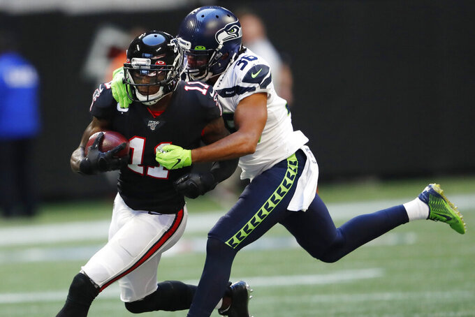 Seattle Seahawks cornerback Akeem King (36) tackles Atlanta Falcons wide receiver Julio Jones (11) during the second half of an NFL football game, Sunday, Oct. 27, 2019, in Atlanta. (AP Photo/John Bazemore)