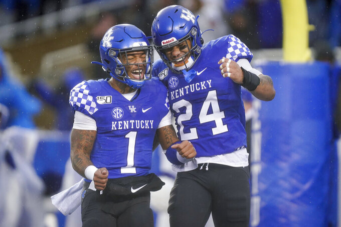 Kentucky quarterback Lynn Bowden Jr. (1) celebrates with running back Christopher Rodriguez Jr. (24) after Rodriguez scored a touchdown during the second half of the NCAA college football game against Louisville, Saturday, Nov. 30, 2019, in Lexington, Ky. (AP Photo/Bryan Woolston)