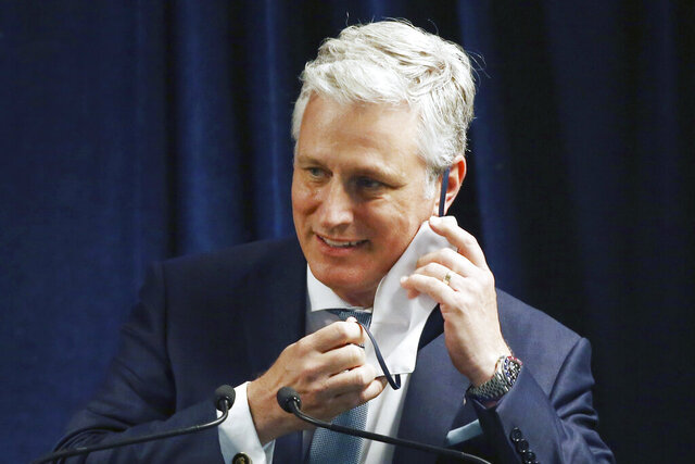 FILE - In this June 24, 2020 file photo, Robert O'Brien, assistant to the president for national security affairs, removes a face covering prior to speaking during a news conference in Phoenix. O'Brien has tested positive for the coronavirus. He's the highest-ranking White House official to test positive so far. (AP Photo/Ross D. Franklin)