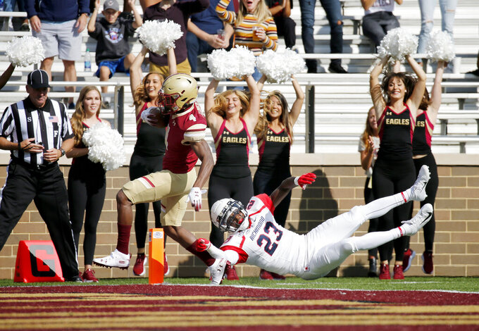 Boston College wide receiver Zay Flowers (4) rushes into the end zone ahead of Richmond defensive back Daniel Jones (23) during the first half of an NCAA college football game, Saturday, Sept. 7, 2019, in Boston. (AP Photo/Mary Schwalm)