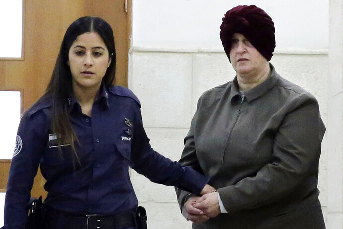 FILE - This Feb. 27, 2018 file photo, Australian Malka Leifer, right, is brought to a courtroom in Jerusalem. An Israeli psychiatric panel has determined that Leifer facing dozens of sex-abuse charges in Australia is fit to stand trial for extradition, the Justice Ministry confirmed Thursday, Jan. 9, 2020. The decision is a major breakthrough in a years-old case that has strained relations between Israel and Australia and upset many members of Australia's Jewish community. (AP Photo/Mahmoud Illean, File)