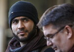 FILE - In this Feb. 26, 2019 photo, former Guantanamo Bay prisoner Omar Khadr and his lawyer Nate Whitling speak with media outside the courthouse in Edmonton, Canada. A Canadian judge ruled on Monday, March 25, 2019 that a war crimes sentence for Khadr expired, meaning he no longer faces the threat of returning to prison. The Canadian-born Khadr was 15 when he was captured by U.S. troops at a suspected al-Qaida compound in Afghanistan. (Jason Franson/The Canadian Press via AP, File)