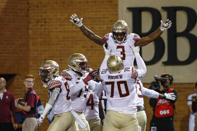 Florida State offensive lineman Cole Minshew (70) lifts running back Cam Akers after Akers scored a touchdown against Wake Forest in the first half of an NCAA college football game in Winston-Salem, N.C., Saturday, Oct. 19, 2019. (AP Photo/Nell Redmond)