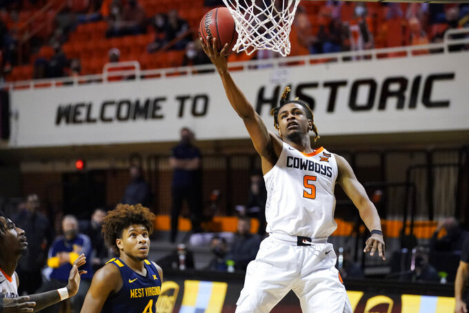 Oklahoma State guard Rondel Walker (5) shoots in front of West Virginia guard Miles McBride, left, in the second half of an NCAA college basketball game Monday, Jan. 4, 2021, in Stillwater, Okla. (AP Photo/Sue Ogrocki)