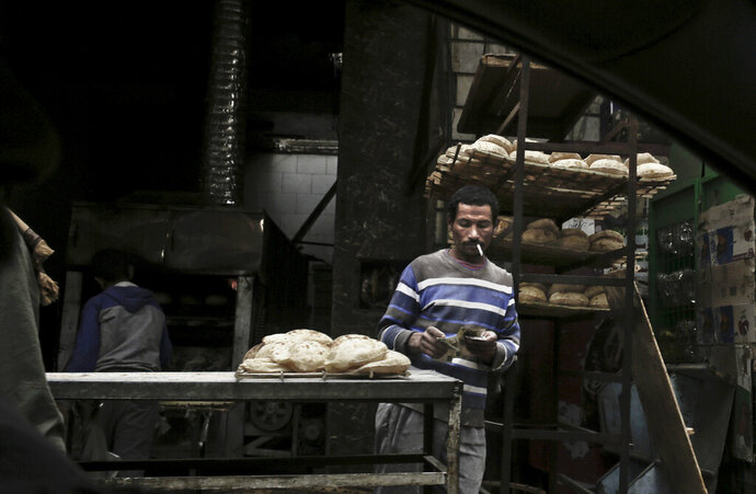 FILE - In this Feb. 14, 2017 file photo, a vendor counts his money at a bread stand in the Sayeda Zeinab neighborhood of Cairo, Egypt. A Monday, July 29, 2019 report said one in every three Egyptian citizens was living in poverty in 2018. The country's statistics agency said 32.5% of Egyptians lived below the poverty line that year, up from 27.8% in 2015 and 16.7% in 2000. Monday's report was the first on poverty and income since the government secured a $12 billion loan from the International Monetary Fund in 2016. (AP Photo/Nariman El-Mofty, File)