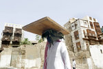A man, wearing a face masks as a precaution against the spread of the coronavirus, carries a tray as he walks at Jiddah's historical district, in Jiddah, Saudi Arabia, Monday, June 15, 2020. This was supposed to be Saudi Arabia's year to shine as host of the prestigious G20 gathering of world leaders. The country had only just begun to swing open its doors to tourists and eye-popping concerts when the coronavirus pandemic upended the crown prince's roadmap of reforms. Due to the pandemic, the gathering this November will likely be a virtual meet-up.  (AP Photo/Amr Nabil)