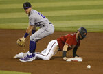 Colorado Rockies shortstop Trevor Story, left, looks for the ball after Arizona Diamondbacks' Wyatt Mathisen dove back into second base during the fourth inning of a baseball game Sunday, Sept. 27, 2020, in Phoenix. (AP Photo/Darryl Webb)