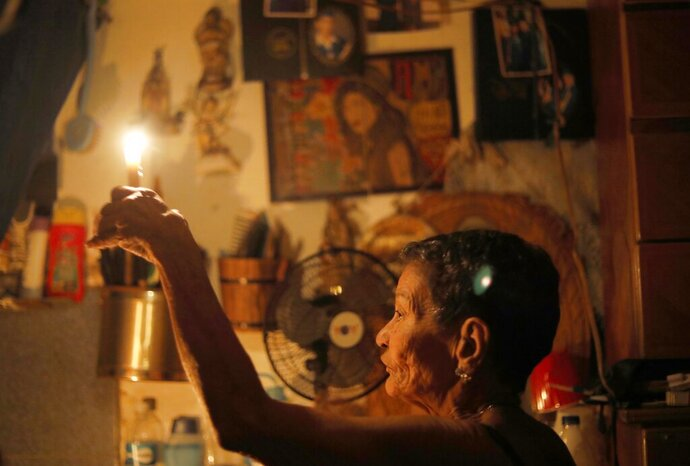 """72-year-old Elizabeth Guzman Espitia holds a candle in herwindowless room she calls her """"little cave"""" during a blackout in the Santa Cruz of the East neighborhood, in Caracas, Venezuela, Thursday, March 14, 2019. I've never see a crisis like this. It's the first time,"""" Espitia said. """"It makes me so sad."""" Venezuela's power grid crashed March 7, throwing almost all of the oil-rich nation's 30 million residents into chaos for nearly a week. (AP Photo/Ariana Cubillos)"""