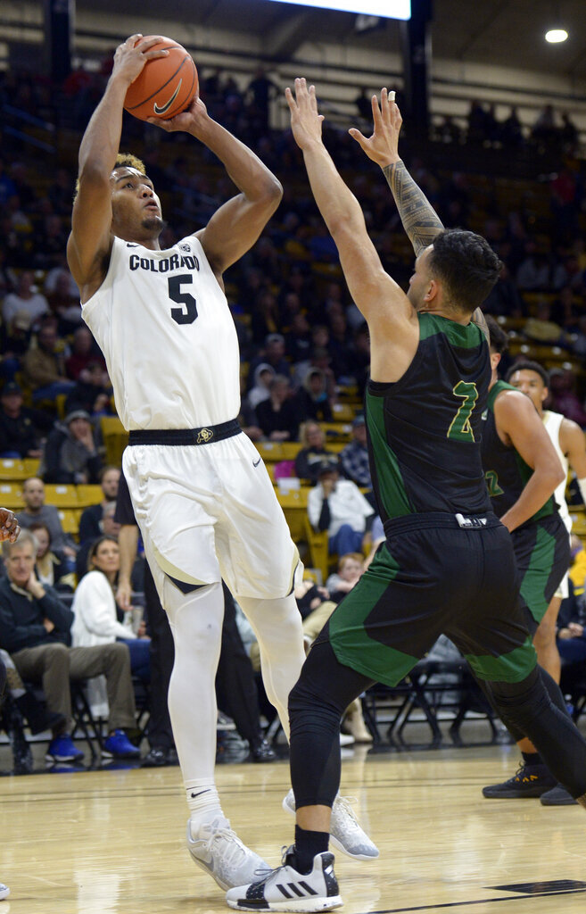 Colorado guard D'Shawn Schwartz, left, shoots over Sacramento State guard Izayah Mauriohooho-Le'Afa in the first half of an NCAA college basketball game, Saturday, Nov. 30, 2019, in Boulder, Colo. (AP Photo/Cliff Grassmick)