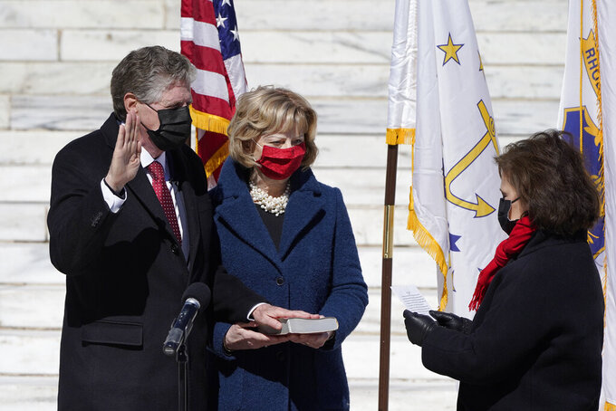 Rhode Island Democratic Gov. Dan McKee, left, is ceremonially sworn in by R.I. Secretary of State Nellie Gorbea, right, as his wife Susan McKee, center, holds the family Bible during an inauguration ceremony, Sunday, March 7, 2021, in front of the Statehouse, in Providence, R.I. (AP Photo/Steven Senne)
