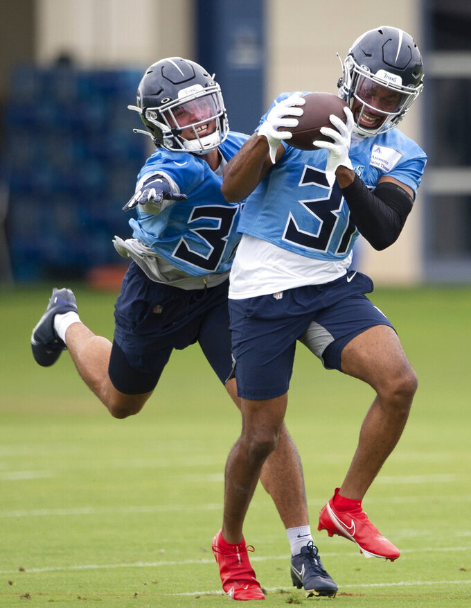 Tennessee Titans safety Kevin Byard (31) pulls in a pass against safety Amani Hooker, left, during an NFL football practice Thursday, June 10, 2021, in Nashville, Tenn. (George Walker IV/Pool Photo via AP)