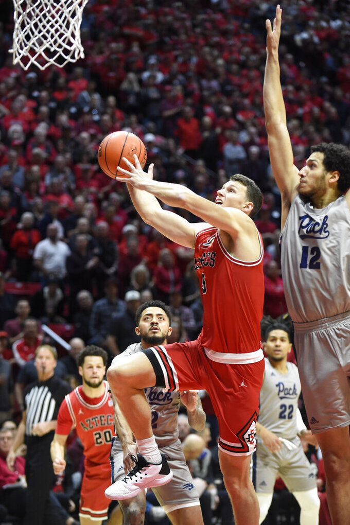 San Diego State forward Yanni Wetzell (5) shoots past the defense of Nevada forward Johncarlos Reyes (12) during the first half of an NCAA college basketball game Saturday, Jan. 18, 2020, in San Diego. (AP Photo/Denis Poroy)