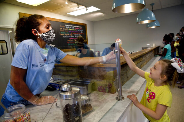 Hallie Chewing, 19, a rising junior at Liberty University serves customer, Kora Mayo, 6, a cookie dough with rainbow sprinkles cone at Blue Cow Ice Cream on July 13, 2020, in Roanoke, Va. Owner Carolyn Kiser said she's seen an increase in job applications, although Blue Cow hasn't needed to hire as many workers as usual. She said the ice cream shop typically employs a lot of students. (Stephanie Klein-Davis/The Roanoke Times via AP)