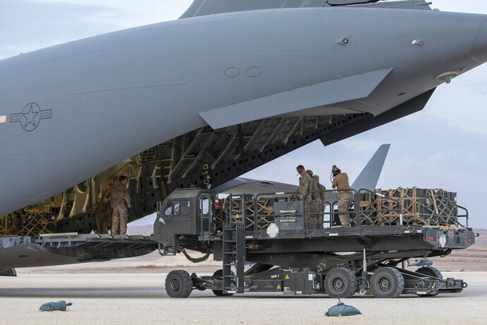 In this Oct. 24, 2019, photo, U.S. service members load military equipment from an aircraft cargo loader onto a plane at the Kobani Landing Zone (KLZ), Syria. Pivoting from the dramatic killing of the Islamic State group's leader, the Pentagon is increasing U.S. efforts to protect Syria's oil fields from the extremist group as well as from Syria itself and the country's Russian allies. It's a new high-stakes mission even as American troops are withdrawn from other parts of the country.(U.S. Army Reserve photo by Staff Sgt. Joshua Hammock via AP)