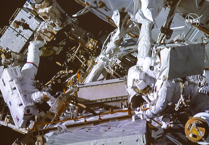 Canadian astronaut David Saint-Jacques, right, and NASA astronaut Anne McClain take part in a spacewalk as seen in the live feed from the Canadian Space Agency headquarters in St. Hubert, Quebec, Monday, April 8, 2019. The pair tackled battery and cable work outside the International Space Station on Monday. (NASA/Canadian Space Agency/The Canadian Press via AP)