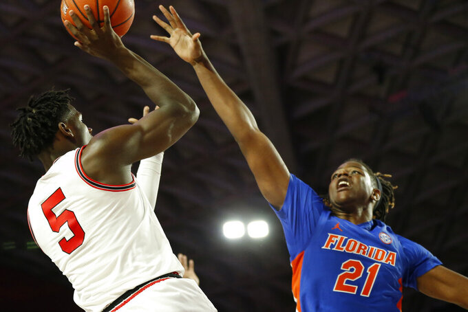Georgia's Anthony Edwards (5) tries to get a shot past Florida forward Dontay Bassett (21) during an NCAA college basketball game Wednesday, March 4, 2020, in Athens, Ga. (Joshua L. Jones/Athens Banner-Herald via AP)