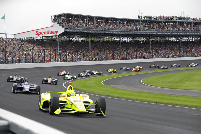 "FILE - In this May 26, 2019, file photo, Simon Pagenaud, of France, leads the field through the first turn on the start of the Indianapolis 500 IndyCar auto race at Indianapolis Motor Speedway in Indianapolis. Roger Penske has reversed course and decided not to allow fans at the Indianapolis 500 later this month. The 104th running of ""The Great American Race"" will be the first without spectators, who showed up at Indianapolis Motor Speedway every year, even during the Great Depression. (AP Photo/Darron Cummings, File)"