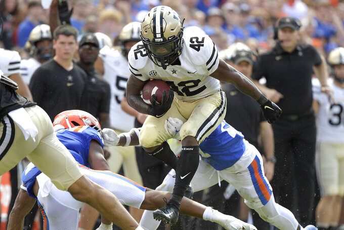 Vanderbilt running back Patrick Smith (42) rushes for yardage in front of Florida linebacker Mohamoud Diabate, left, and cornerback Jadarrius Perkins, rear, during the first half of an NCAA college football game, Saturday, Oct. 9, 2021, in Gainesville, Fla. (AP Photo/Phelan M. Ebenhack)