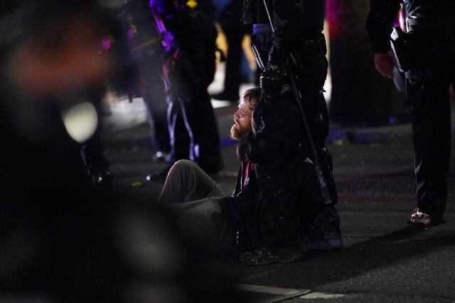 Portland police arrest a man during protests, Saturday, Sept. 26, 2020, in Portland. The protests, which began over the killing of George Floyd, often result frequent clashes between protesters and law enforcement. (AP Photo/John Locher)